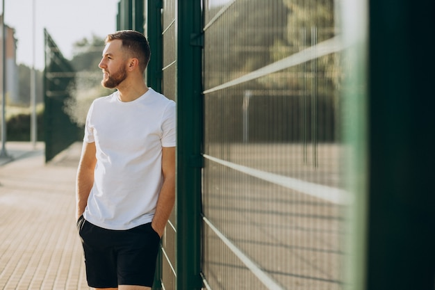 Young man standing at stadium in the morning