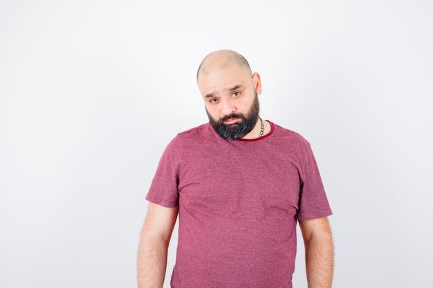 Молодой человек стоит прямо и позирует перед камерой в розовой футболке и выглядит серьезным, вид спереди.
