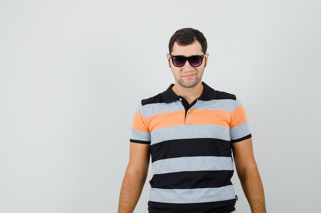 Young man standing in t-shirt,sunglasses and looking cool. front view. space for text