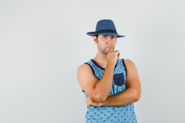 Giovane che sta nel pensiero posa in singoletto blu, cappello e sembra serio. vista frontale.