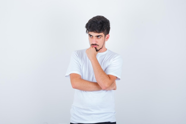 Giovane uomo in piedi in posa di pensiero mentre distoglie lo sguardo in maglietta e sembra pensieroso