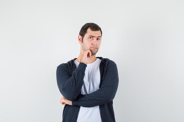 Giovane che sta nella posa di pensiero in maglietta bianca e felpa con cappuccio nera con zip e sembra serio, vista frontale.