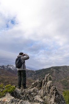 Young man standing on top of cliff in winter mountains at daytime