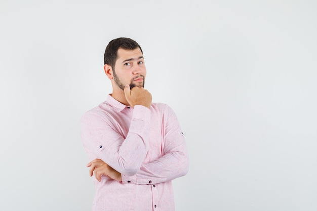 Giovane uomo in piedi mentre pensa in camicia rosa e sembra bello