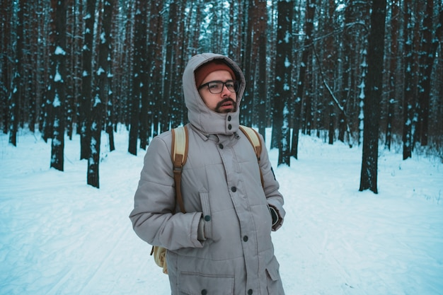 Young man standing in winter snowy forest