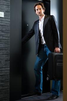 ホテルの部屋のドアの前にトロリーを持って立っている若い男