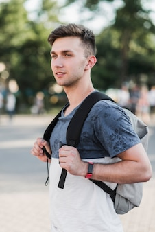 Young man standing with backpack