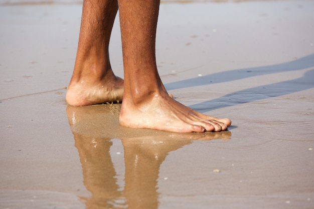 Young man standing with bare feet on beach