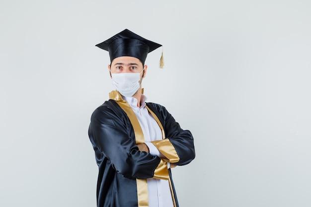 Giovane uomo in piedi con le braccia incrociate in uniforme laureato e guardando fiducioso. vista frontale.