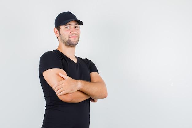 黒のtシャツで腕を組んで立っている若い男