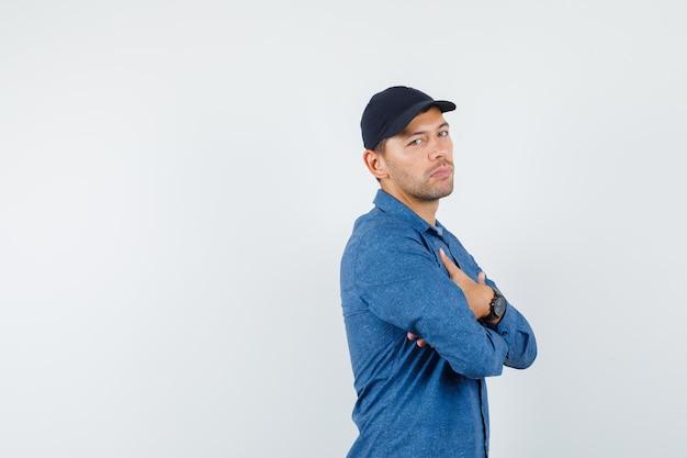 青いシャツ、キャップ、自信を持って腕を組んで立っている若い男。