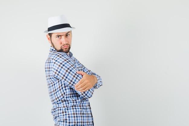 Молодой человек стоял со скрещенными руками в клетчатой рубашке, шляпе и выглядел серьезно.