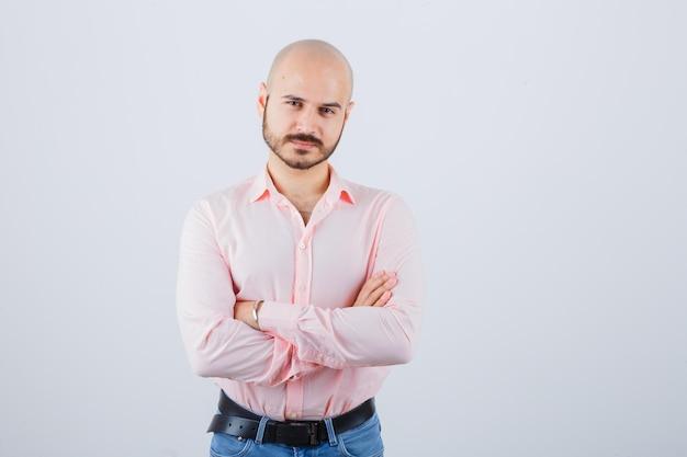 ピンクのシャツ、ジーンズ、自信を持って腕を組んで立っている若い男。正面図。
