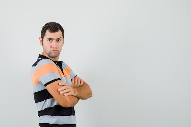 Молодой человек стоял со скрещенными руками в футболке и выглядел серьезно. передний план. свободное место для вашего текста