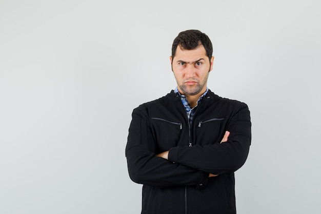 Young man standing with crossed arms in shirt, jacket and looking serious. front view.