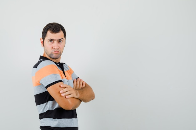 Giovane che sta con le braccia incrociate in maglietta e che sembra serio. vista frontale. spazio libero per il testo