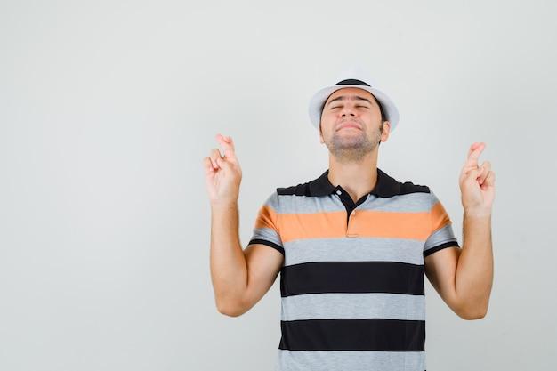 縞模様のtシャツ、帽子、落ち着いて見える交差した指で立っている若い男。正面図。テキスト用のスペース