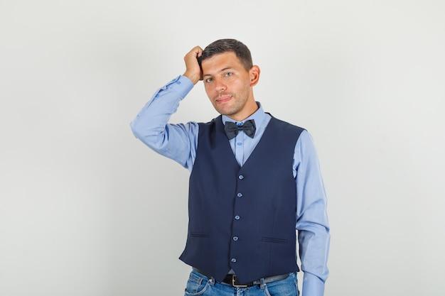Молодой человек, стоящий с рукой на голове в костюме, джинсах и задумчивый.
