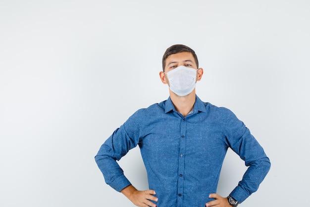 파란색 셔츠, 마스크, 심각한 찾고 허리에 손으로 서 있는 젊은 남자. 전면보기.