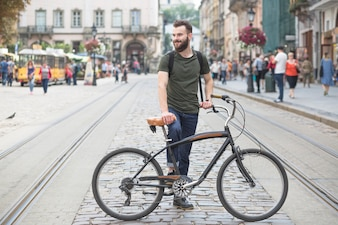 Young man standing with his bicycle in city