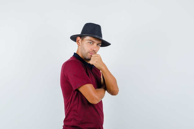 티셔츠, 모자에 주먹을 들고 서 있는 청년, 자신감 있는 앞모습.