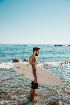 Young man standing with surfboard in blue water