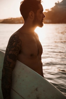 Young man standing with surfboard in sea