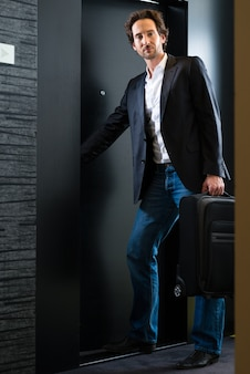 Young man standing with a trolley in front of a room door in a hotel