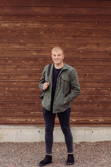 Young man standing next to a wooden wall