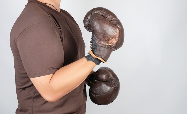 Young man stands in a boxing rack, wearing very old vintage brown boxing gloves on his hands