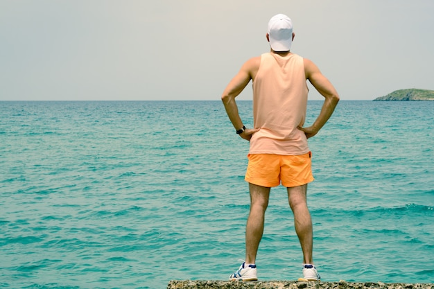 A young man stands on the edge of the pier, looks into the distance