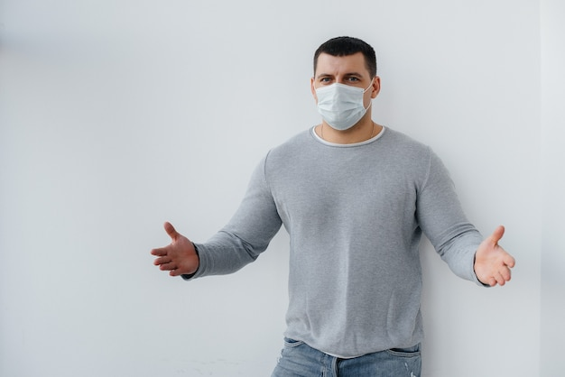 A young man stands on a gray wall wearing a mask during a quarantine with free space. quarantine in the mask.
