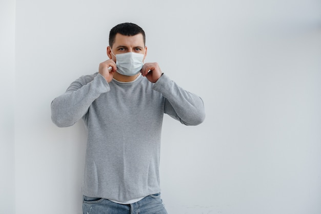 Young man stands on gray wearing mask during quarantine with free space. quarantine in the mask.