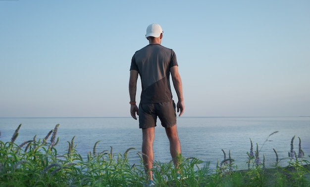A young man stands on a hill by the sea. back view.
