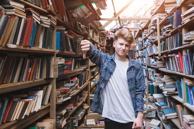 若い男が公共図書館に立って、指を下に見せる。
