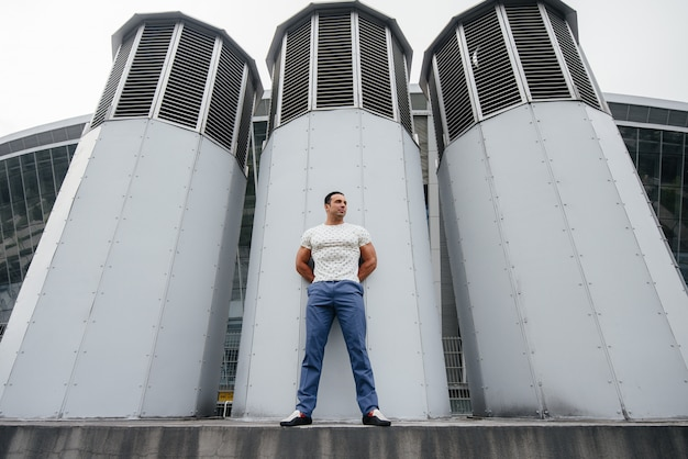 Молодой человек стоит на открытом воздухе возле технических сооружений.