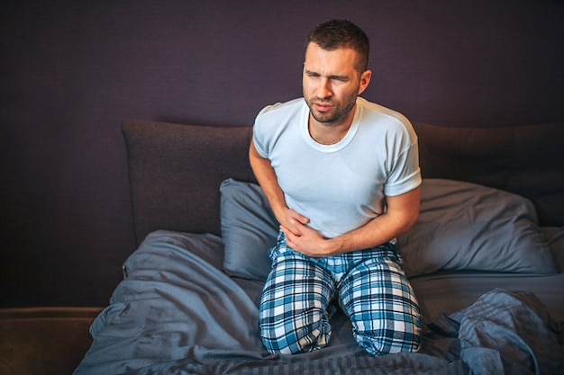 Young man stands on knees on bed and suffers from pain in appendix area. he holds hands there. guy shrinks. he wear pajamas.