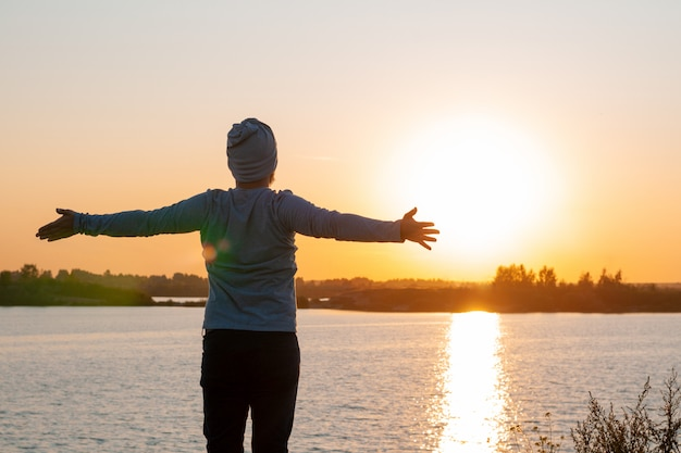 A young man stands on a lake at sunset