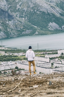A young man stands on a mountain and looks at a beautiful landscape