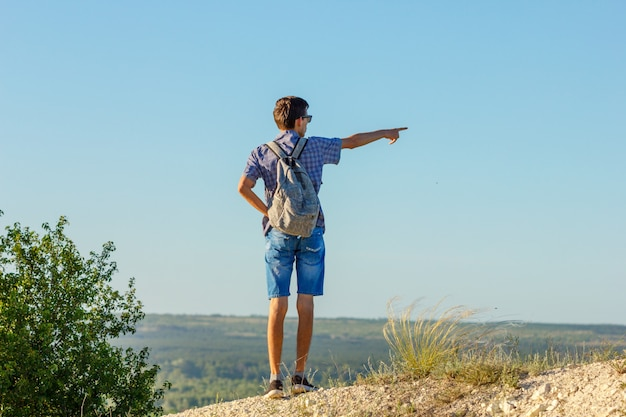 A young man stands on a mountain and looks into the distance showing a hand direction
