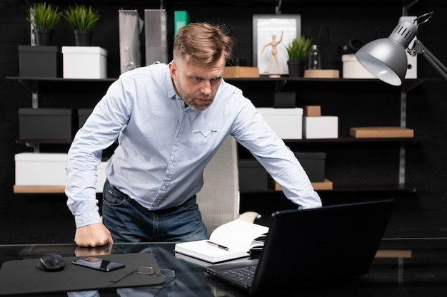 Young man stands near the computer table and looks at the monitor
