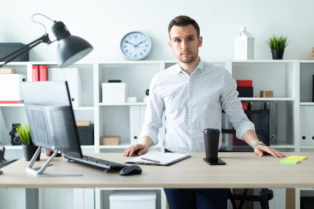 A young man stands near a table in the office
