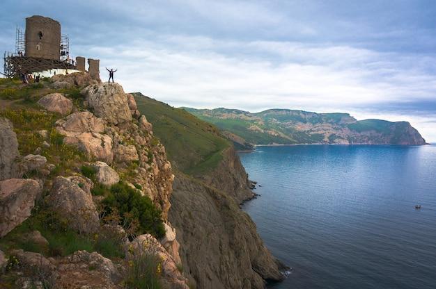 Молодой человек стоит на краю пропасти, глядя вдаль на море. балаклава, крым. на фоне старинной крепости