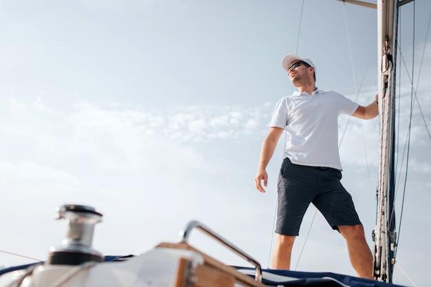 Молодой человек стоит на борту яхты и смотрит вперед. он держит мачту со стороны. молодой человек позирует. он носит белую рубашку и черные шорты.
