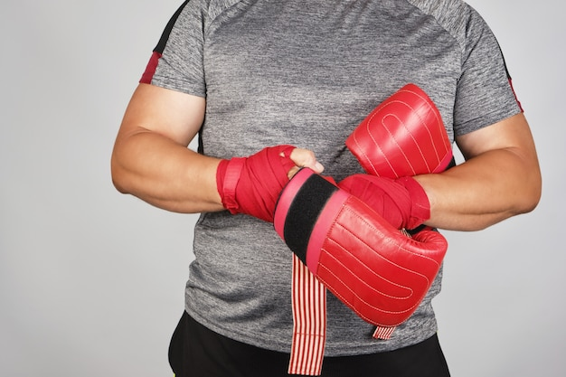 Young man stands and puts on his hands red boxing gloves