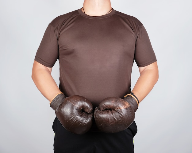 Young man stands wearing very old vintage brown boxing gloves on his hands