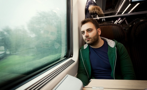 Young man staring out the train window.