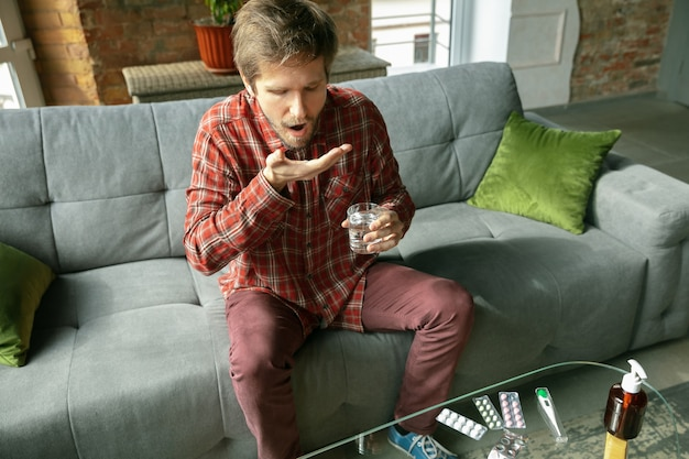 Young man staying at home, drinking water and taking pills