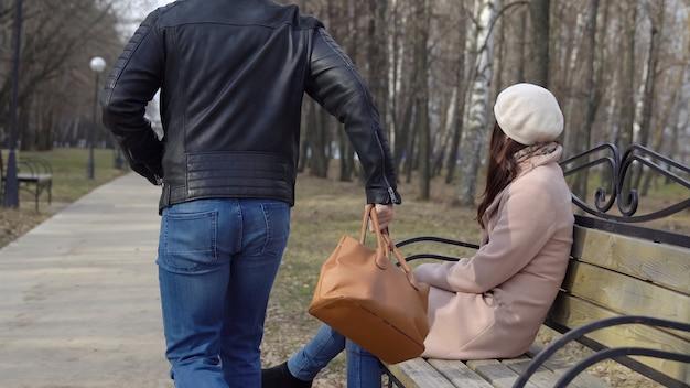 Молодой человек крадет женскую сумку со скамейки в парке и бежит.