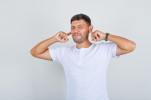 Молодой человек вставляет пальцы вилки в уши в белой футболке и выглядит напряженным, вид спереди.
